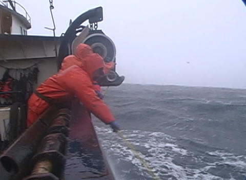 lobster fishermen struggle to attach a rope to a machine on their crab fishing boat during a raging Footage