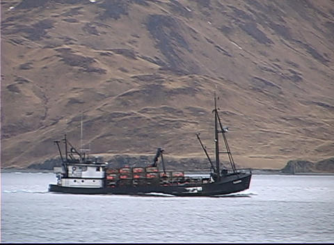 A large ship pushes a crabber vessel across the ocean Stock Video Footage