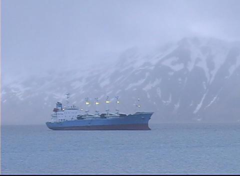 A bird flies above a large vessel on a calm sea Footage