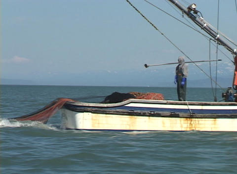 A fisherman watches as a large net is cast into the ocean from the back of his boat Footage