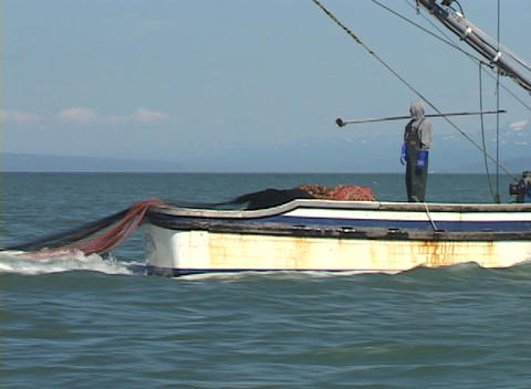 A fisherman watches as a large net is cast into the ocean... Stock Video Footage