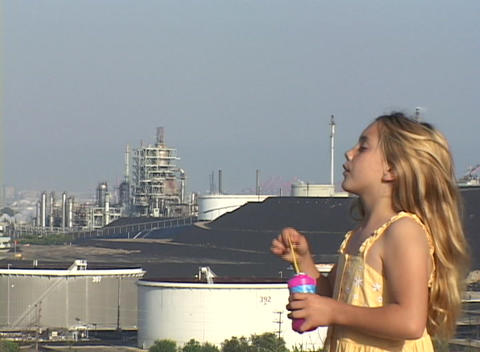An adorable blonde girl blows bubbles as she overlooks an... Stock Video Footage