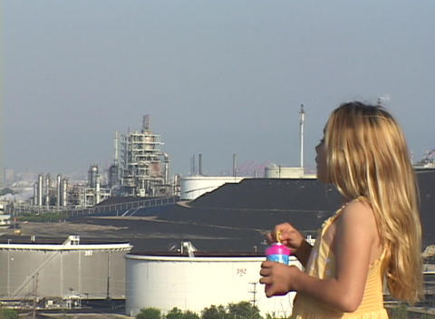 An Adorable Blonde Girl Blows Bubbles As She Overlooks An Industrial Area stock footage
