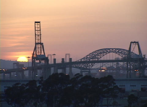 Bridges and industrial buildings are in silhouette against the golden sky Footage