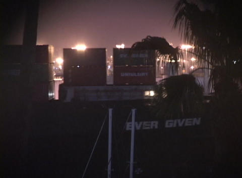 Medium shot of giant cargo container ship entering a port at night Footage