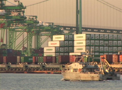 Medium shot of a boat passing cargo containers in a busy port Footage