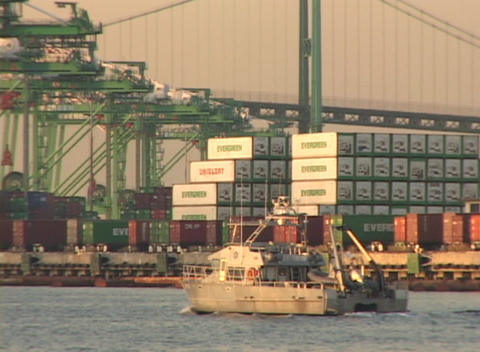 Medium shot of a boat passing cargo containers in a busy... Stock Video Footage