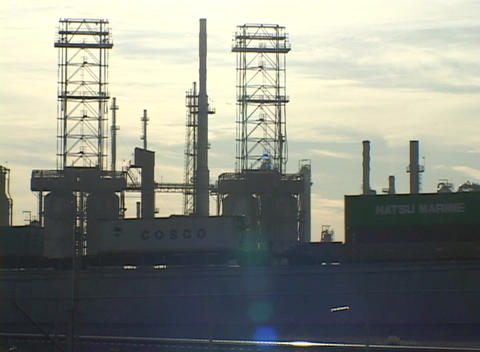 Medium shot of train traveling beside an oil refinery Footage