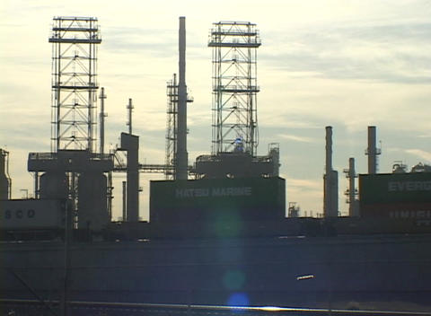 Medium shot of train traveling beside an oil refinery Stock Video Footage