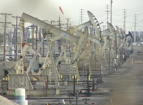 Medium shot of oil derricks pumping in a large oil field Footage