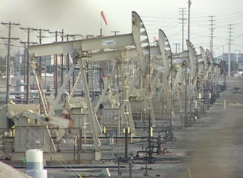 Medium shot of oil derricks pumping in a large oil field Stock Video Footage