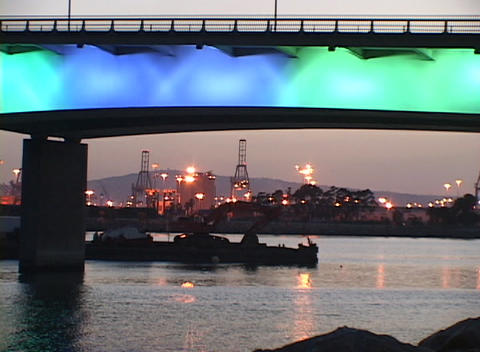 Tracking-out of an oil refinery and colorfully-lighted bridge Footage