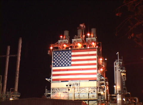 Zoom-out from an American flag at an oil refinery Footage