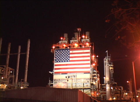 Zoom-out from an American flag at an oil refinery Stock Video Footage