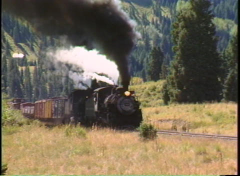 Pan-right shot of a steam train chug through the Colorado mountains Footage
