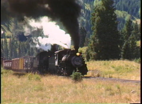 Pan-right shot of a steam train chug through the Colorado... Stock Video Footage