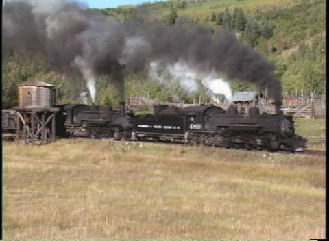 Medium shot of a steam freight train passing a water tower Footage