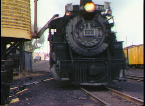 Medium shot of a steam freight train passing a water tower Stock Video Footage
