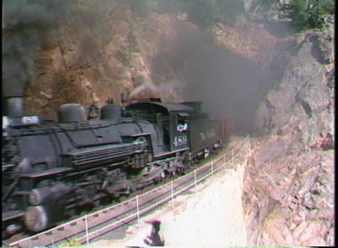 Pan-left shot of a Rio Grande steam freight train chug through a tunnel in a Colorado mountainside Footage