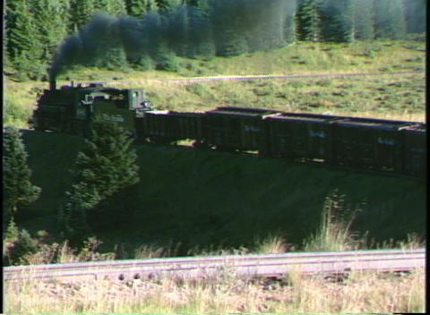 Following shot of a Rio Grande steam freight train traveling through a Colorado mountain valley Footage
