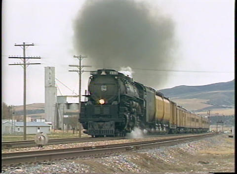 Pan-left shot of a Union Pacific steam train passing by grain silos in a small Colorado town Footage