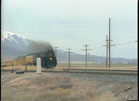 Pan-right shot of a fast moving steam passenger train Stock Video Footage