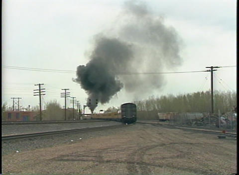Medium shot of a steam train disappearing down the tracks Stock Video Footage