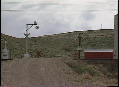 Medium shot of a train speeding through a railroad crossing Stock Video Footage