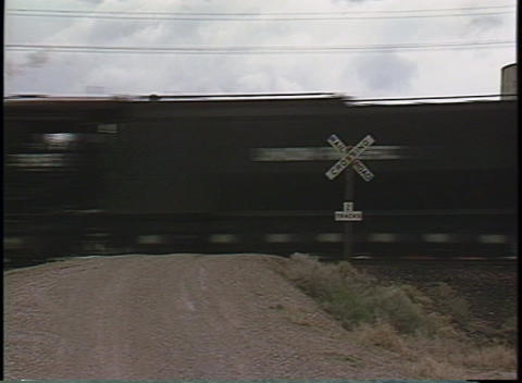 Medium shot of a train speeding through a railroad crossing Stock Video Footage