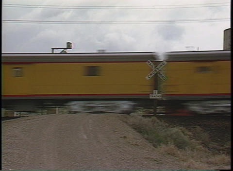 Medium shot of a train speeding through a railroad crossing Footage