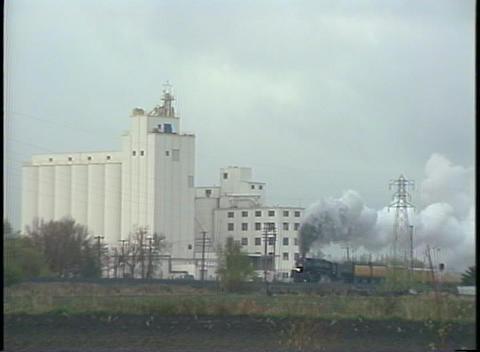 Long-shot of a steam passenger train speeding by a... Stock Video Footage