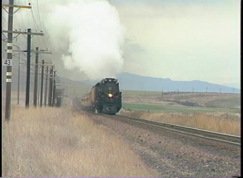 Tracking-right shot of a steam passenger train racing... Stock Video Footage