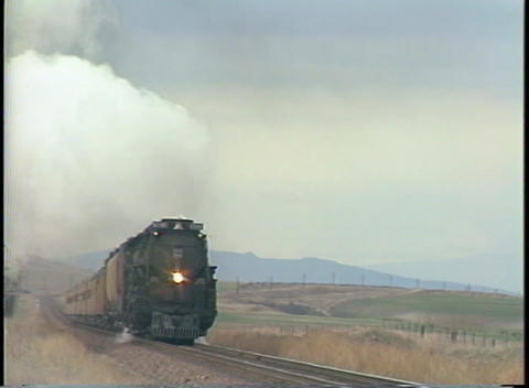 Tracking-right Shot Of A Steam Passenger Train Racing Down The Tracks stock footage