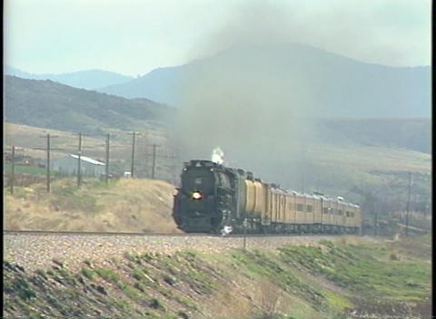 Tracking-left shot of a steam train speeding down the tracks Stock Video Footage