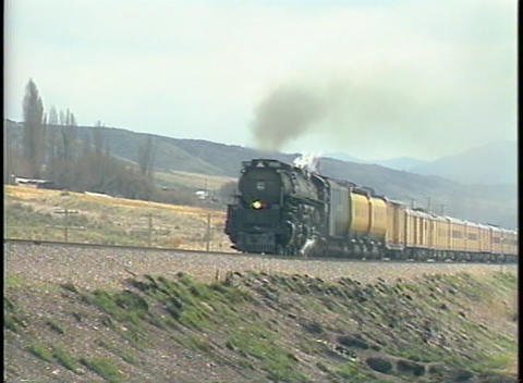 Tracking-left shot of a steam train speeding down the tracks Footage