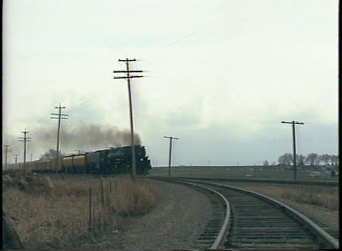 Pan-right shot of a steam passenger train passing by at a... Stock Video Footage