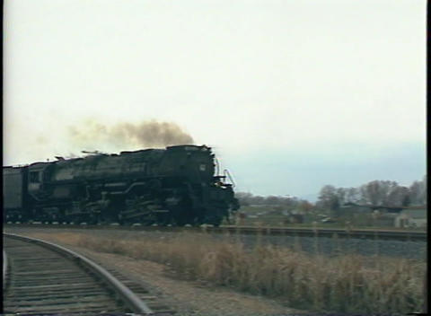 Pan-right shot of a steam passenger train passing by at a high rate of speed Footage