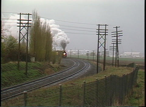 Following shot of a steam passenger train rounding a bend Stock Video Footage