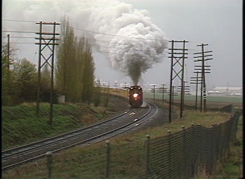Following shot of a steam passenger train rounding a bend Footage