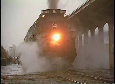 Pan-left shot of a steam passenger train at a station on a rainy day Footage