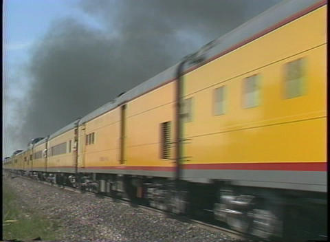 Tracking shot of a steam passenger train speeding through the countryside Footage