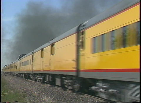 Tracking shot of a steam passenger train speeding through... Stock Video Footage