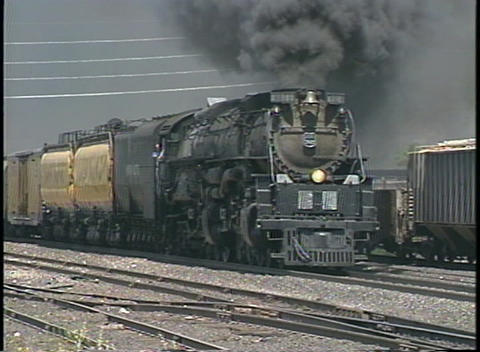 Tracking shot of a steam train passing through a freight... Stock Video Footage