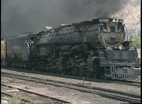 Tracking shot of a steam train passing through a freight yard Footage