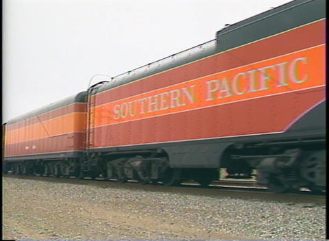 Medium shot of a Southern Pacific steam passenger train passing by slowly Footage