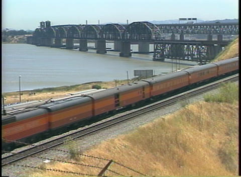 Zoom-out of a Southern Pacific train passing by a large highway bridge Footage