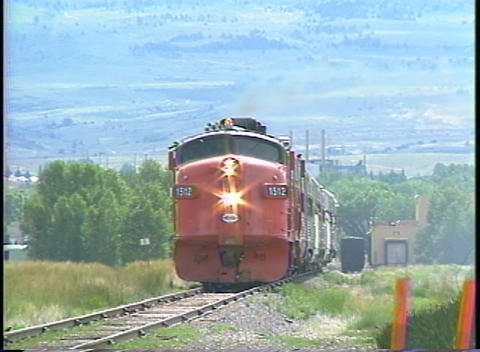 Pan-left shot of a diesel engine pulling a passenger... Stock Video Footage