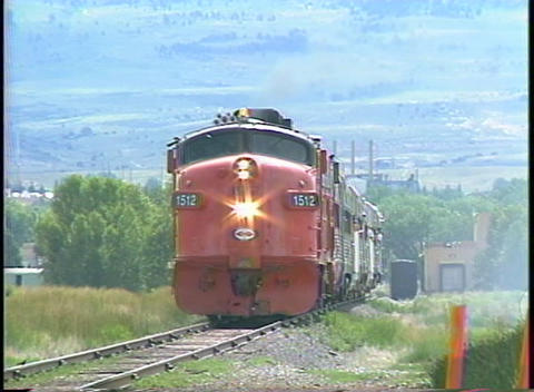 Pan-left shot of a diesel engine pulling a passenger train through the countryside Live Action