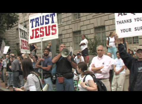 Handheld-shot walking through a religious anti-war protest Footage