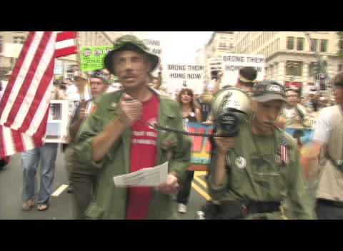 Medium-shot of anti-Iraq-war protestors marching in Washington, DC Footage